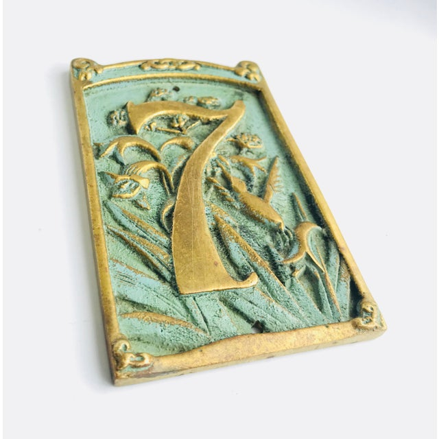 Vintage house plaque number « 7 », solid brass with a shabby bluish turquoise paint. Botanical carved pattern with a bird....