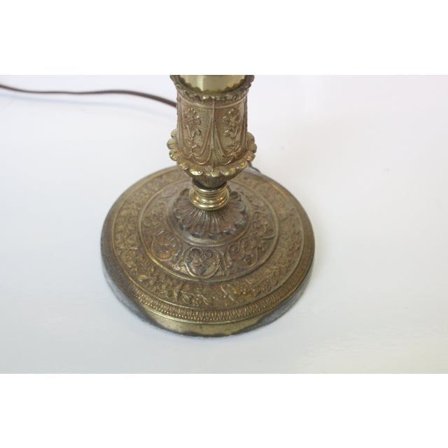 A brass Greek Revival desk lamp with a festooned base, Corinthian column and a laurel of olive branches as the finial....