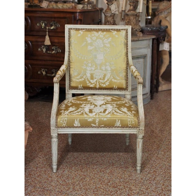 Epoch Louis XVI single armchair with square back, upholstered in a french cream and gold jacquard fabric. Urn with flowers...