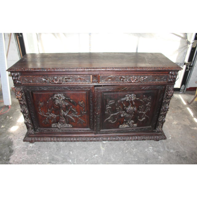 Made of solid oak and situated on bun-style feet, this piece is a superior quality antique cabinet. Hand-carved foliate...