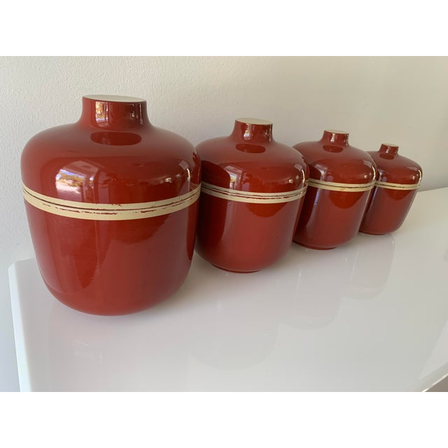 Set of 4 Lacquer Ware Nesting Jars marked S S Lacquer Ware, made in Japan. Brick red and tan accents. Large jar measures...