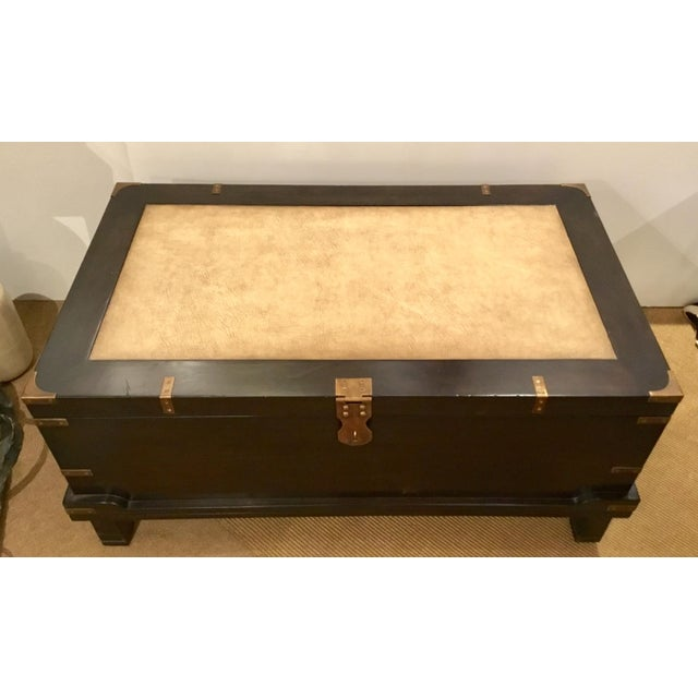 Stylish Currey & Co. transitional dark wood coffee table trunk prototype, rich cream leather top, antique brass metal accents