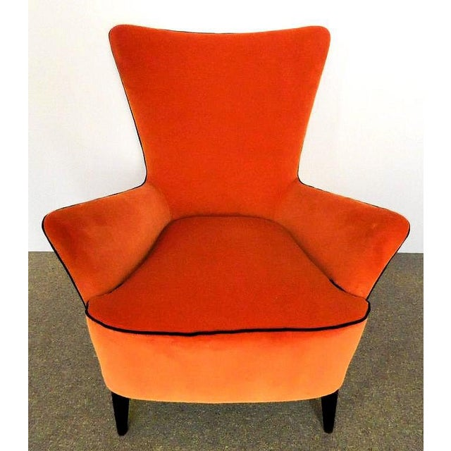 Pair of Mid-Century Modern Italian armchairs with dark wood legs. Newly upholstered with orange velvet, with an elegant...