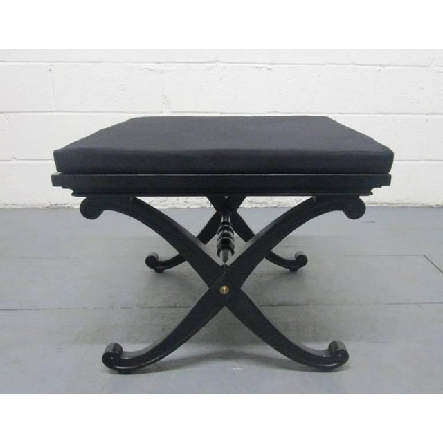 Two X benches in the manner of Maison Jansen. Has a removable cushioned seat. The benches are black with brass accents....