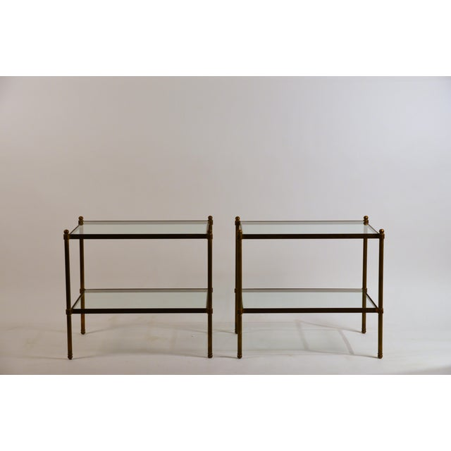 Pair of chic Maison Baguès style patinated solid brass and glass side tables. Shelves are at 9 in. and 21.5 in. from the...