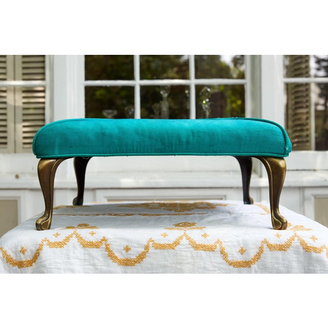 Charming Hollywood Regency square footstool with four brass cabriole legs and a one tuft upholstered top with oversized...