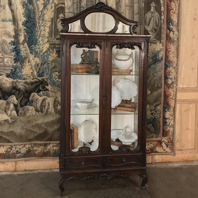 19th Century French Louis XV Marble Top Vitrine is a study in the style, with graceful French scrolls adorned with hand-...
