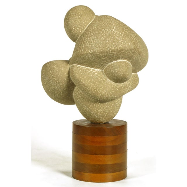 """Carved stone sculpture mounted on a stacked wood cylinder base entitled """"Dancers"""" by noted sculptor, Robert """"Bob""""..."""