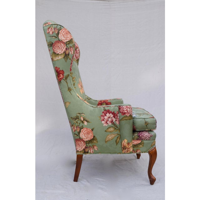 French-style wingback chair attributed to Baker furniture. Features elegant, elongated back, scrolled arms, and carved...