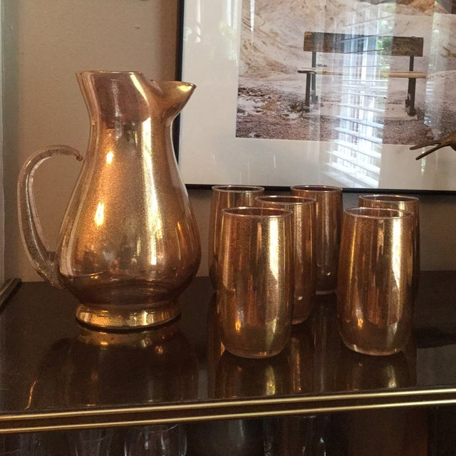 A Mid-Century pitcher and set of six glasses made of an amethyst glass with a graduated gold speckled metallic finish.