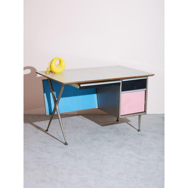 Vintage industrial desk by Raymond Loewy. Features blue peg board back, pink laminate drawer, black laminate drawer, and a...