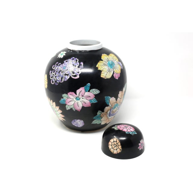 """A vintage, hand-painted ceramic melon jar, with black glaze and colorful flowers. Excellent vintage condition. 10 3/4"""" x 8..."""
