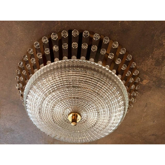 A glamorous 1950s Austrian golden polished brass ceiling light with numerous crystal beads and a cut-glass shade. Three-...