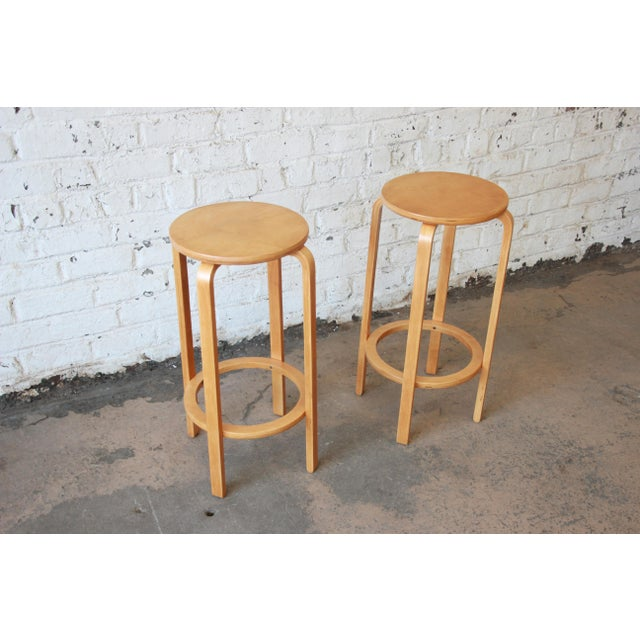 Offering a gorgeous pair of bent birch wood bar stools designed in 1935 by iconic designer Alvar Aalto for Artek. The...