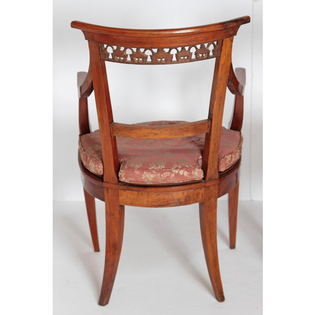 An elegant pair of neoclassical Italian walnut arm chairs. A nicely carved crest rail with a gilded trellis. Loose cushion...