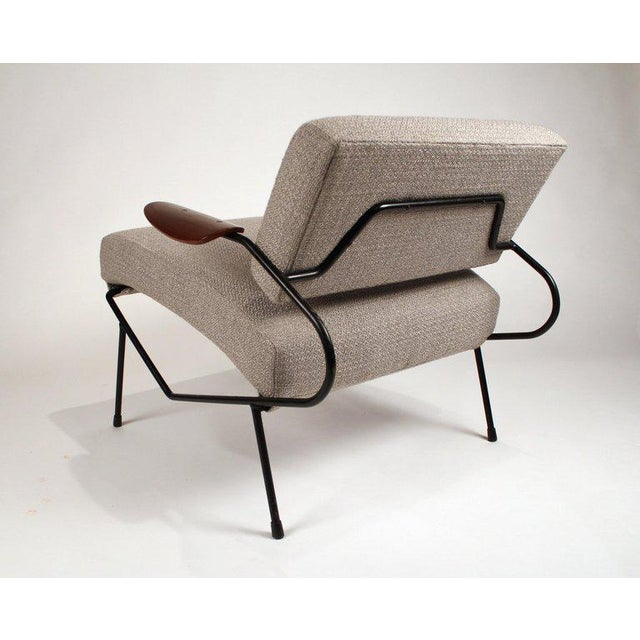 Early Dan Johnson lounge chair with an iron frame and steam bent walnut plywood armrests.