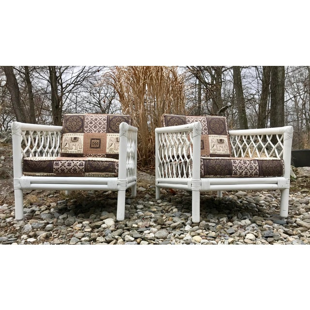 Supreme mid century style is what you get with this pair of rattan latticed arm chairs in white by Willow and Reed....