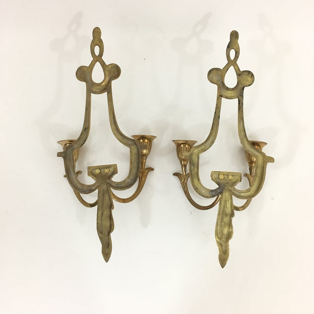 Stunning pair of brass candlestick holders. Each sconce holds two taper candles. Beautiful draped / traditional details....