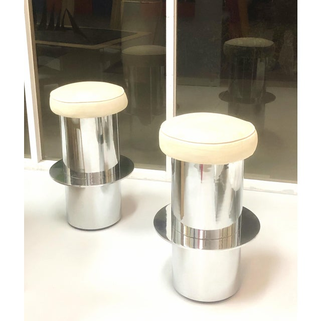 A pair of chrome bar stools with upholstered seats. The metal bases are thick with a solid ring footrest.