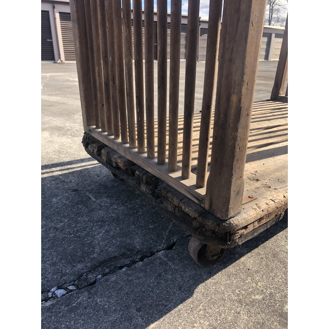 A hand made distressed industrial cart constructed of salvaged wood with two tiers, high sides, and rough big iron...