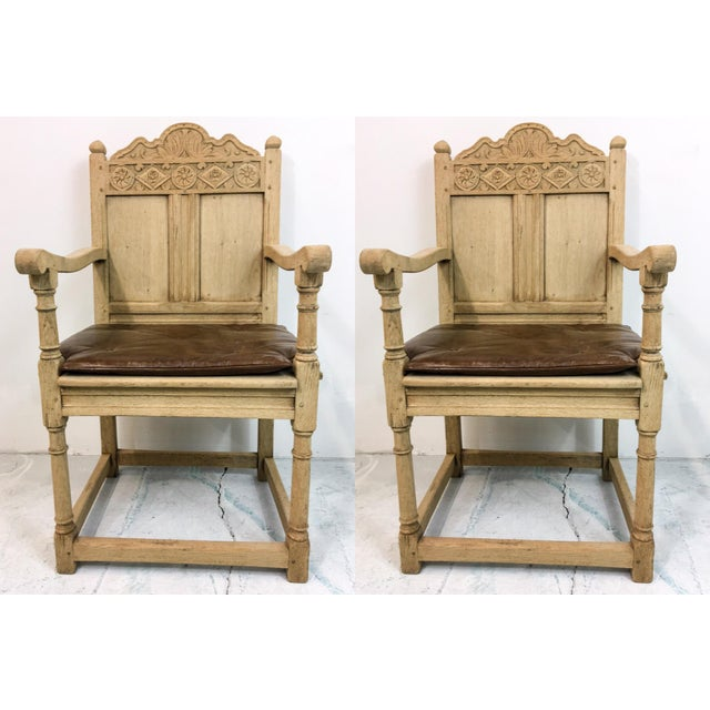 These antique French armchairs have a bleached oak finish and brown tufted leather cushions and box stretcher bases. Arm;...