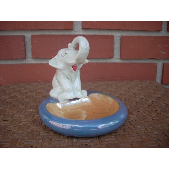 """Marked """"Hand painted Made in Japan"""" opalescent antique white elephant with white tusks and a bright red tongue sits on the..."""