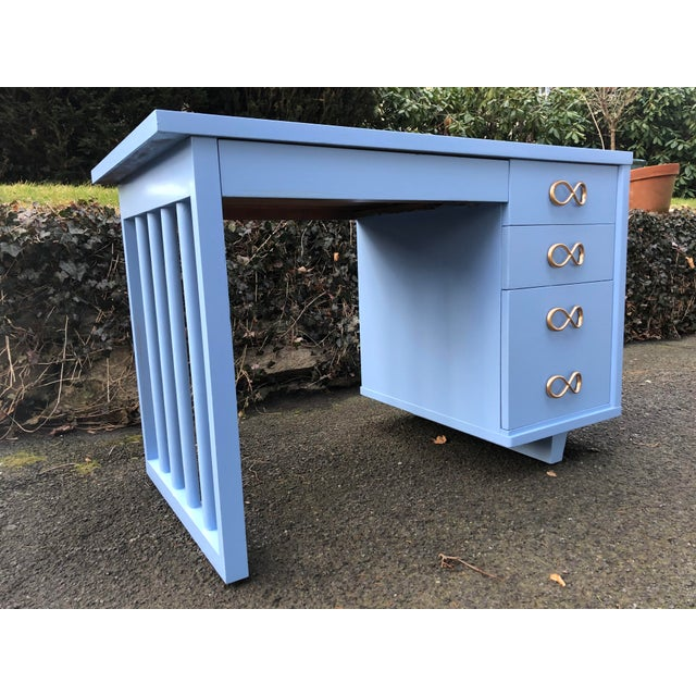 Mid century writing desk. Simplistic functional design. Four drawers in total including one divided drawer and one drawer...