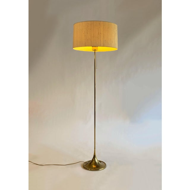A gorgeous and architectural brass floor lamp by Swedish maker Bergboms, model G-025. The lamp features a heavy brass foot...