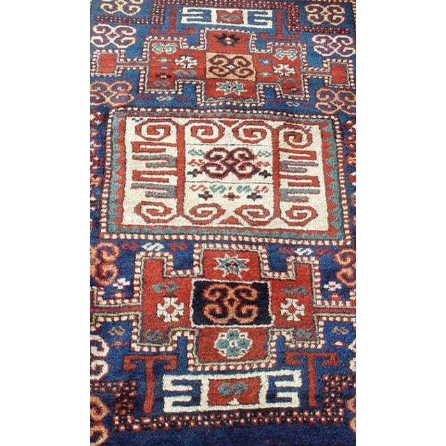 """A wonderfully graphic village rug in primary colors with accents of green, contrasted by an ivory """"leaf and chalice"""" border."""