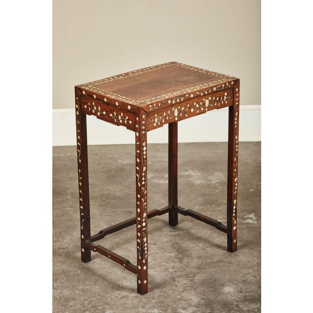 A 19th century Chinese side table with mother-of-pearl inlay on rosewood. Intricately inlaid legs and apron, and border...