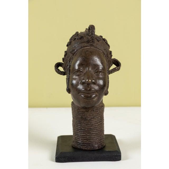 Benin bronze head sculpture on painted wood stand.