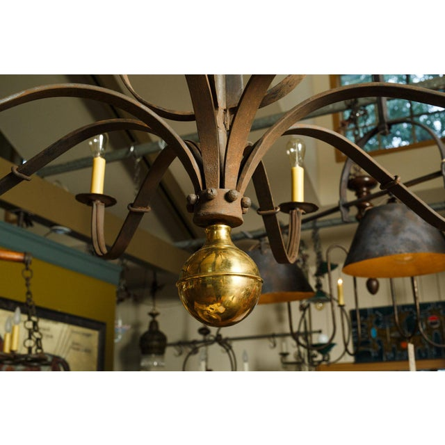 Monumental forged iron chandelier decorated with polished brass finial. Massive iron chandelier hand forged by blacksmith....
