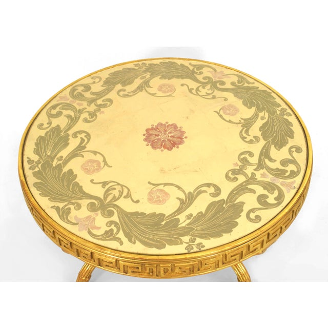 Gilt-wood round coffee table with an églomisé decorated top over a Greek key frieze supported by crossed fluted legs with...