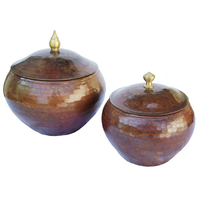 An authentic pair of copper pots in an Arts and Crafts style. These lidded hammered copper pots have an interesting...
