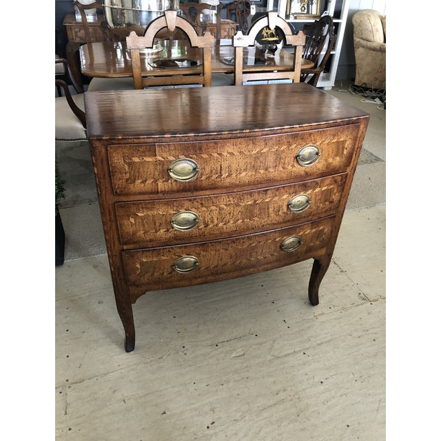 A handsome 3 drawer commode of rich walnut having wonderful inlay decoration around each drawer, brass handles and...