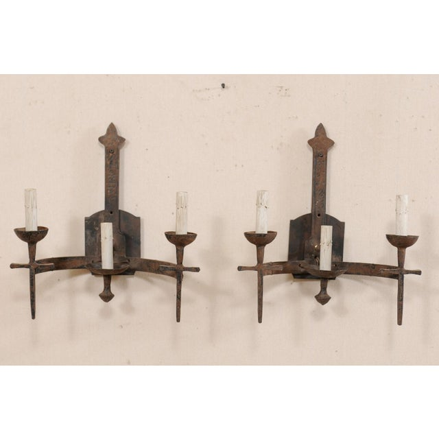 A pair of French three-light iron sconces from the mid-20th century. These vintage French hand forged sconces each have...