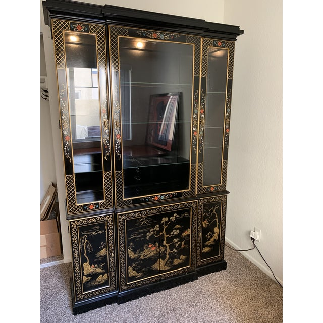 Mid-century Asian display cabinet in black lacquer with gold designs. Adjustable and removable glass shelving allows for...