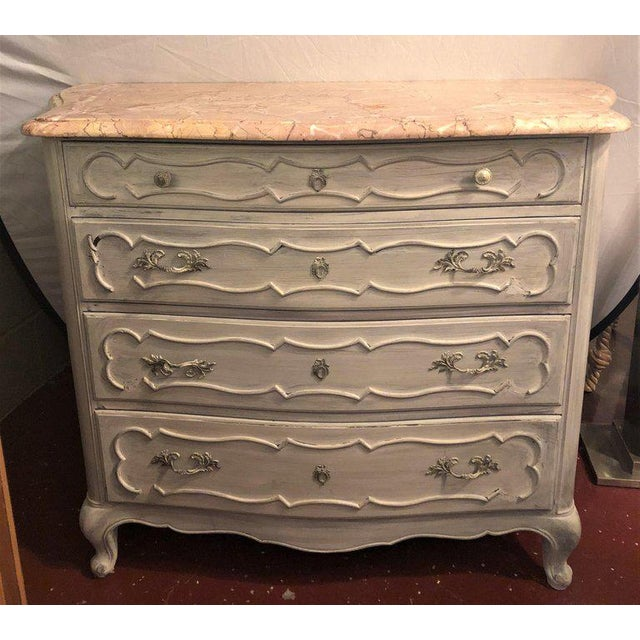 Swedish marble-top four-drawer chest or commode / nightstand. This antiqued French commode or night table has been...