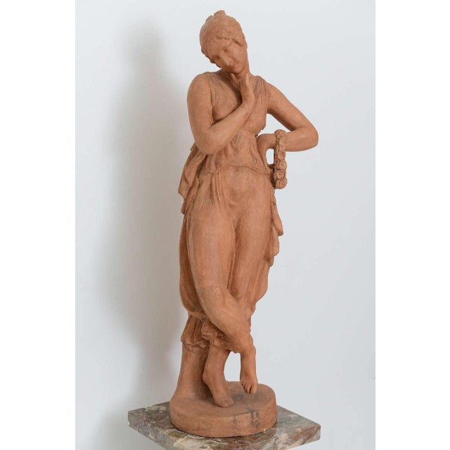 This charming sculpture dates from the early part of the 19th century in France. Here we have a young girl dressed in a...