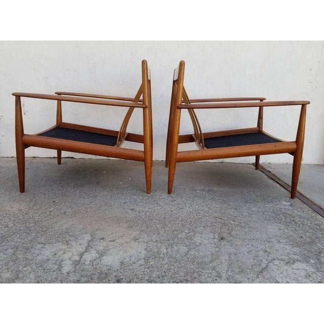 Early pair of Grete Jalk teak lounge chairs by France & Daverkosen, Denmark, circa. 1960. Both chairs retain their...