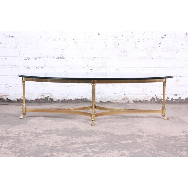 A gorgeous mid-century Hollywood Regency brass and glass coffee or cocktail table by Labarge. The table features a stylish...