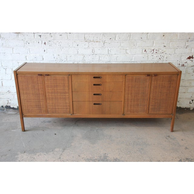 Offering a very nice mid-century modern credenza with woven front doors by Founders. This credenza has two woven front...