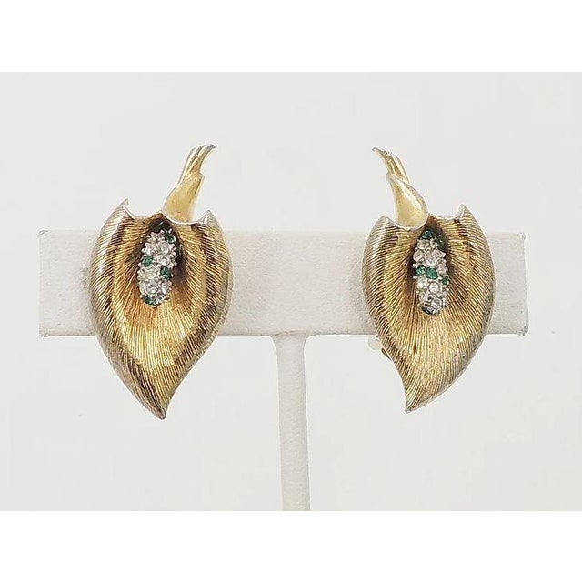 """Goldtone textured calla lilly with faux-emerald and clear paste clip back earrings. Marked """"Boucher"""" with inventory number..."""