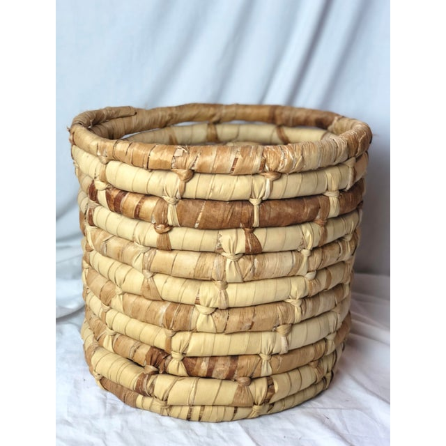 A boho chic basket made of coiled cornhusks. Would be great as a planter or to hold magazines or blankets!