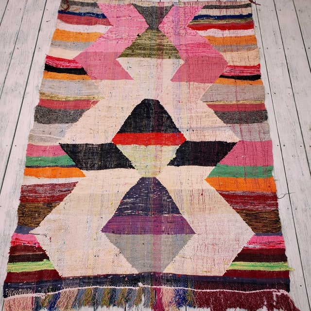This handwoven geometric patterned rug from Morocco gives back with its high impact design and colors. The materials used...