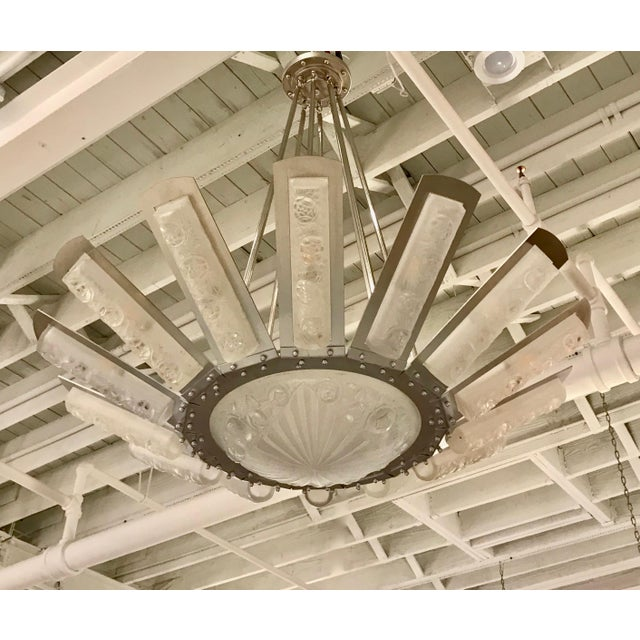 Rare French Art Deco sunburst starburst chandelier signed by French designer Degué. Fourteen glass panels beaming from...