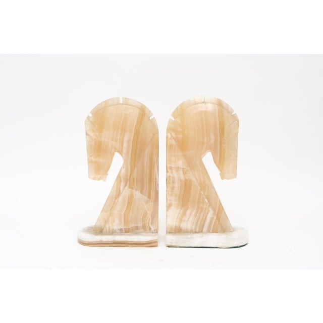 A regal pair of vintage marble horse head bookends. These bookends are sculpted in creamy shades of ivory, camel, and...