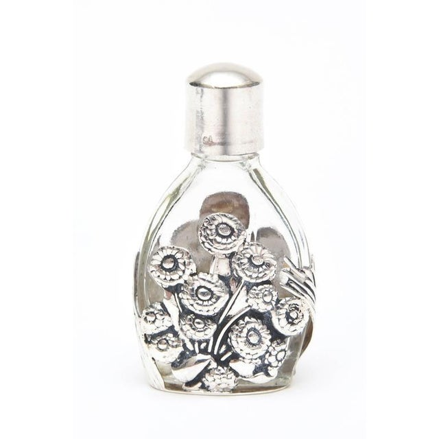 This lovely Art Deco sterling silver raised overlay of a floral design over glass houses your favorite perfume for travel...