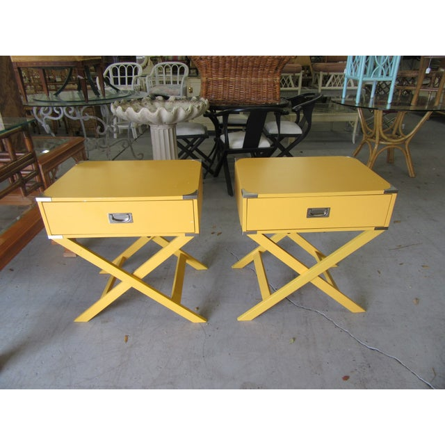 "Pair of yellow campaign style side tables with silver accents. They measure 26"" H x 24"" W x18"" d. It is in good as found..."
