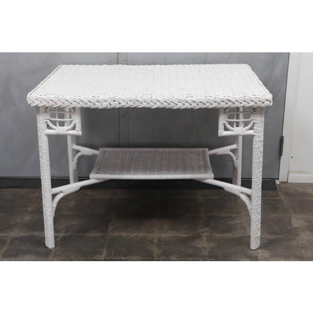 This nice white wicker table has reed woven to a bent wood frame with woven lower shelf and interesting corner details....